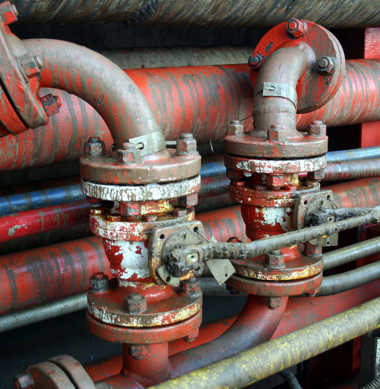 Close up of oil rig piping with red and blue scratched paint