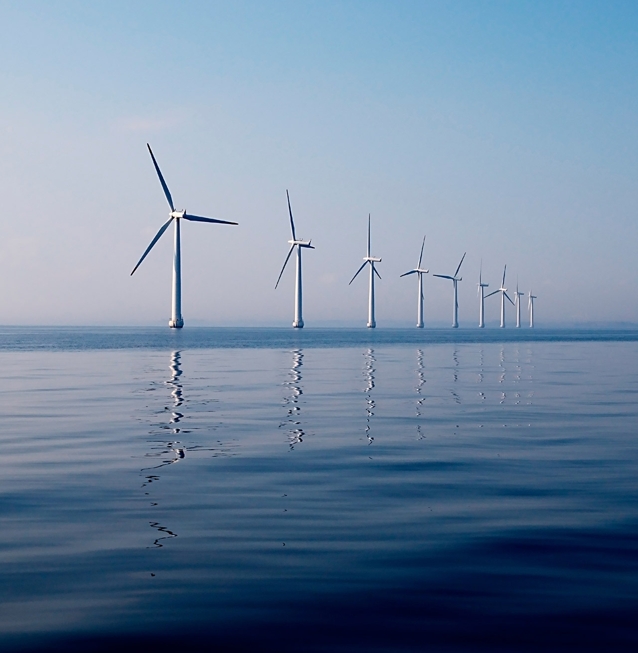 Row of wind turbines in sea, calm water